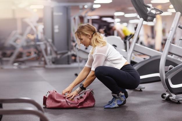 Mulher com sacola vermelha no ginásio