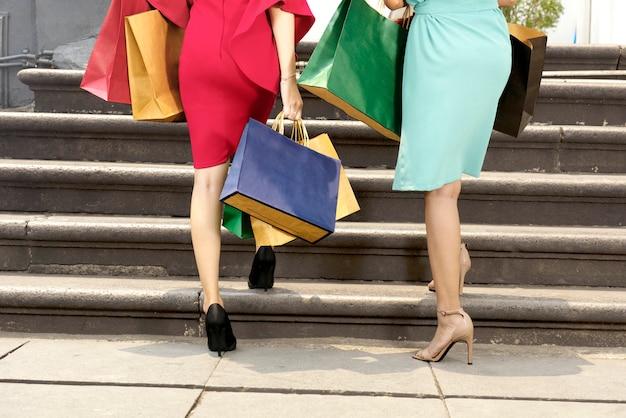 Mulher com sacolas coloridas subindo escadas