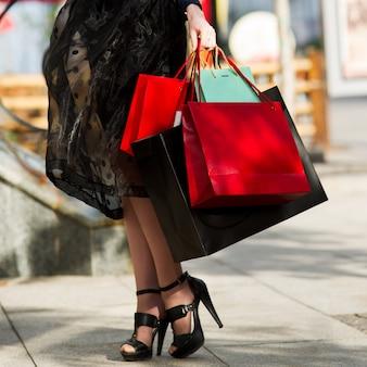 Mulher com sacolas de compras andando pela cidade