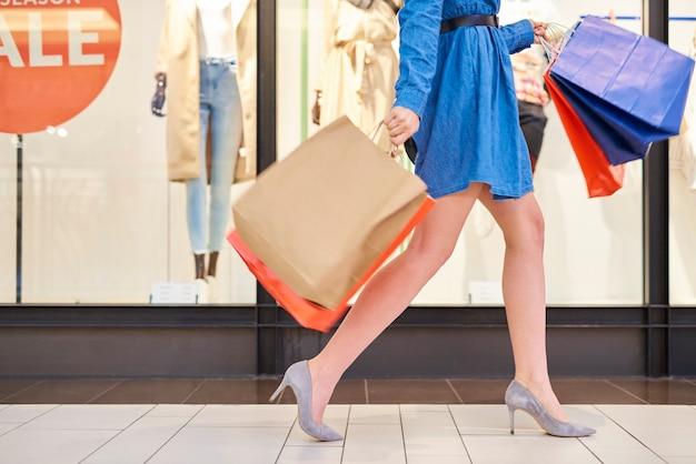 Mulher com sacolas de compras caminhando com pressa