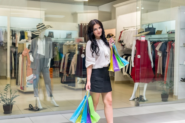 Mulher com sacolas de compras coloridas posando antes da loja de vestidos