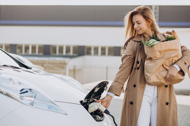 Mulher com sacolas de compras de comida carregando um carro elétrico
