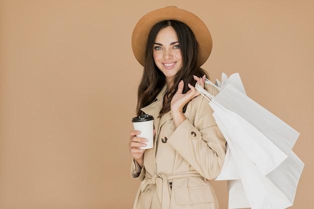 Mulher com sacolas de compras e café sorrindo para a câmera