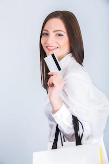 Mulher com sacolas de compras e cartão de crédito