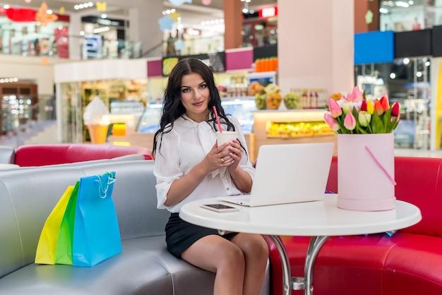 Mulher com sacolas de compras e laptop no café
