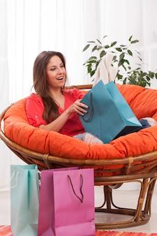 Mulher com sacolas de compras em casa