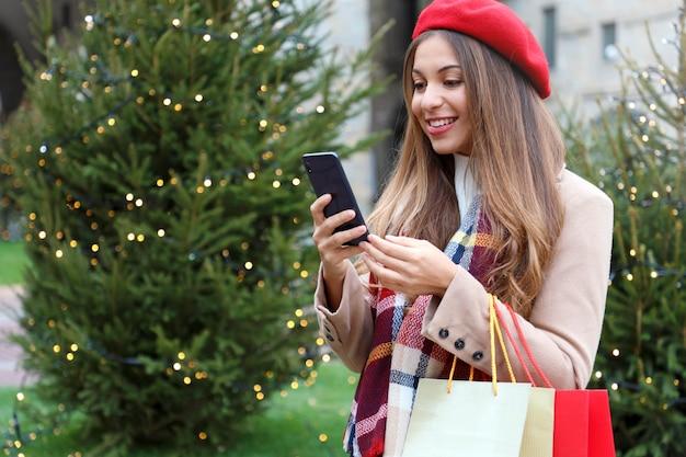 Mulher com sacolas de compras na mão comprando presentes de natal com seu smartphone