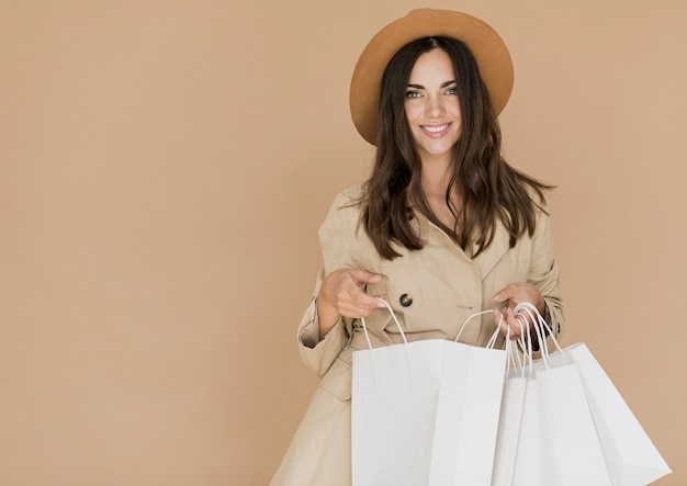 Mulher com sacolas de compras, olhando para a câmera