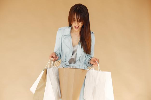 Mulher com sacolas de compras. senhora em uma parede bege. mulher em uma jaqueta azul.
