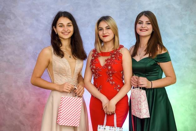 Mulher com sacolas de presente na festa de ano novo, posando em elegantes vestidos de noite