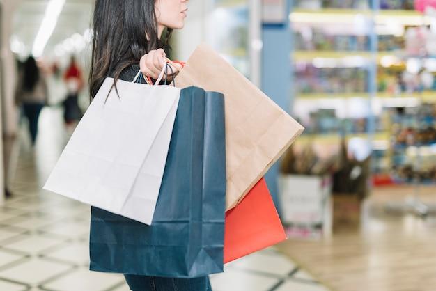 Mulher, com, sacolas papel, em, centro comercial