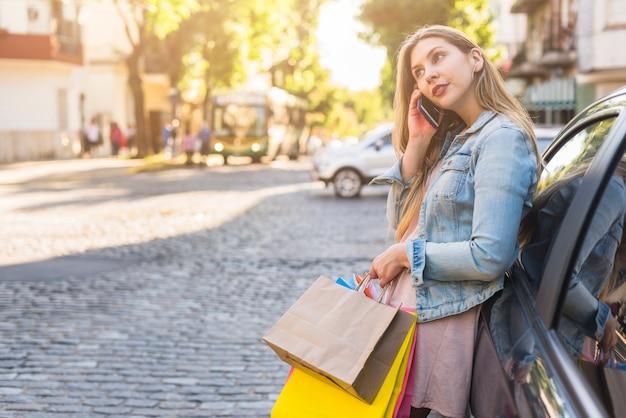 Mulher com sacos de compras brilhantes, falando por telefone na rua