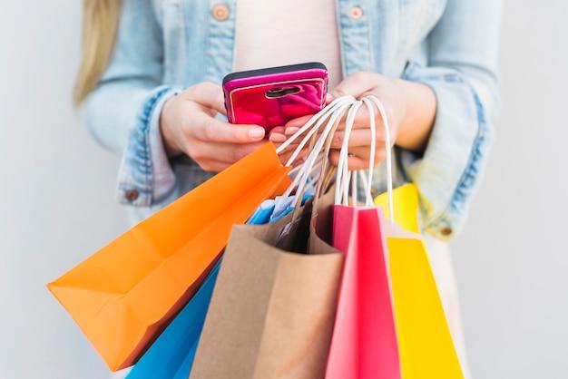 Mulher com sacos de compras brilhantes usando smartphone