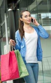 Mulher com sacos de compras está falando por telefone.