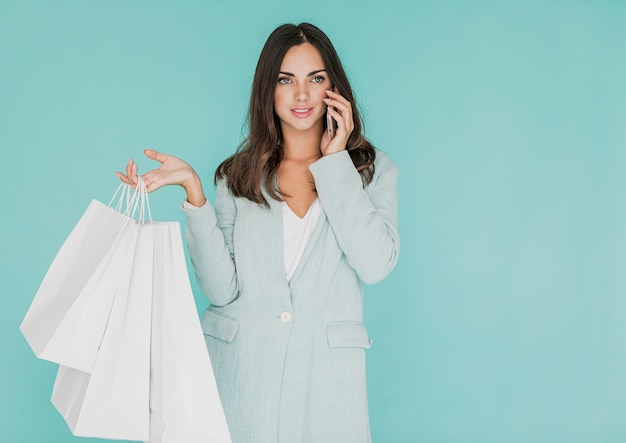 Mulher com sacos de compras, falando ao telefone