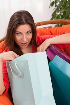 Mulher com sacos de compras surpreso
