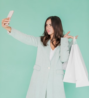 Mulher com sacos de compras, tomando uma selfie