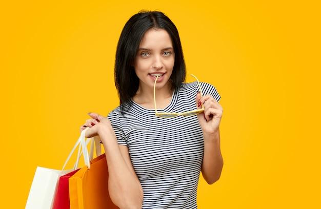 Mulher com sacos de papel mordendo óculos