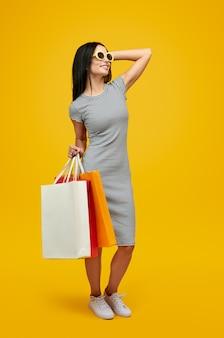 Mulher com sacos de papel olhando para longe