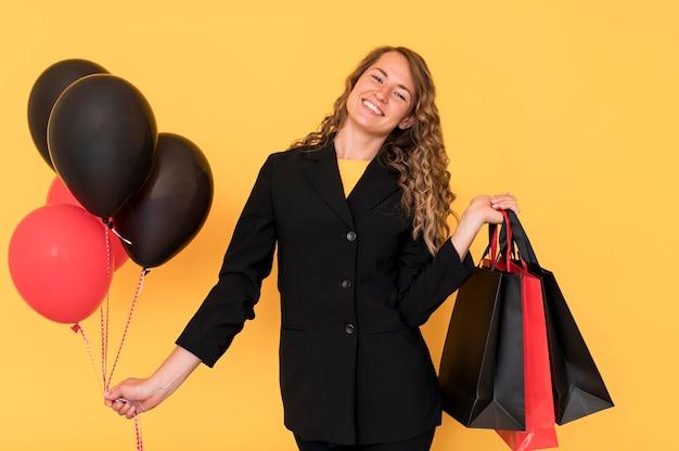 Mulher com sacos pretos e vermelhos com balões
