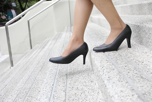 Mulher com sapatos de salto alto, descendo as escadas