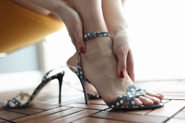 Mulher com sapatos de salto alto segurando uma perna dolorida, closeup