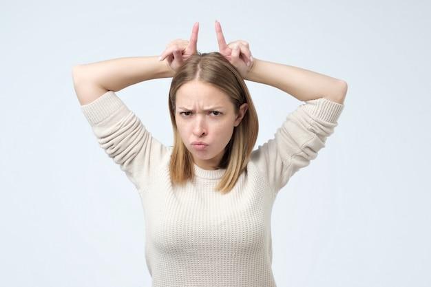 Mulher com sardas apontando para cima com os dedos indicadores atrás da cabeça como se fossem chifres