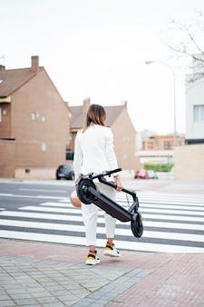 Mulher com scooter elétrica atravessando a rua