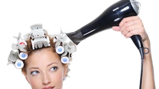 Mulher com secador de cabelo preto secando a cabeça feminina com os cabelos cacheados - close-up