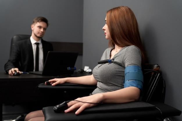 Mulher com sensores de teste no polígrafo de computador.
