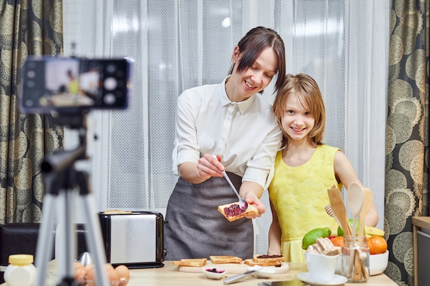 Mulher com seu filho vlogging na cozinha, mãe sorri filha, olha para a câmera, cozinha as tostas com geléia. vloggers preparam comida e compartilham receitas na câmera