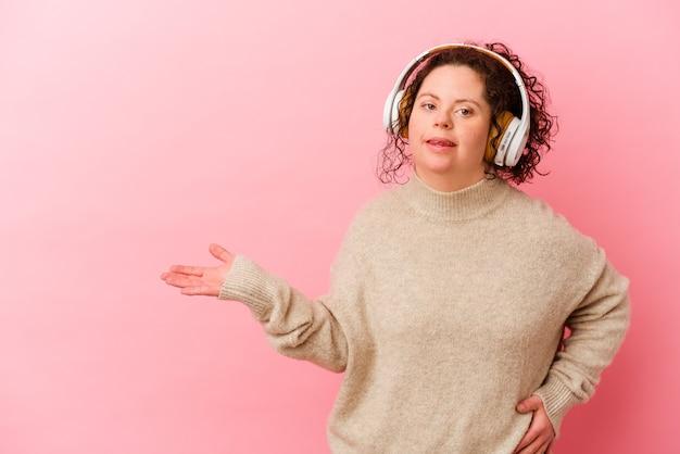 Mulher com síndrome de down com fones de ouvido isolados na parede rosa, mostrando um espaço de cópia na palma da mão e segurando a outra mão na cintura