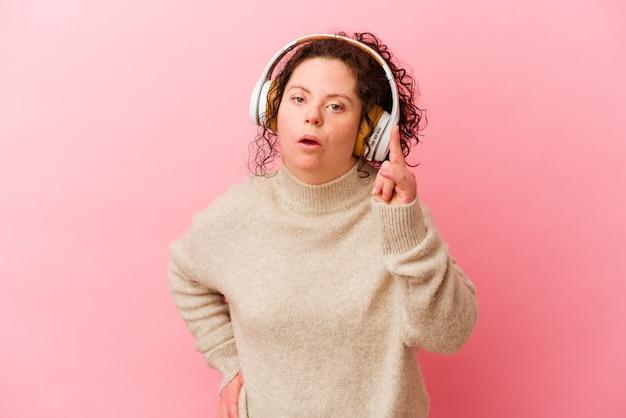 Mulher com síndrome de down com fones de ouvido isolados na parede rosa, tendo uma ideia, o conceito de inspiração.