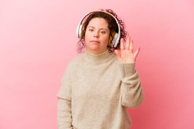 Mulher com síndrome de down com fones de ouvido isolados no fundo rosa, sorrindo alegre mostrando o número cinco com os dedos.