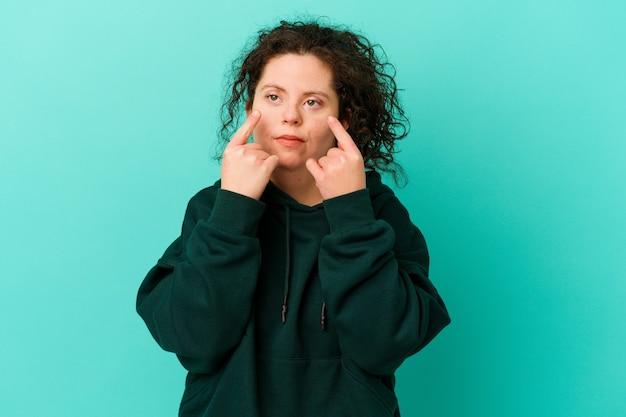 Mulher com síndrome de down isolada chorando, infeliz com algo, conceito de agonia e confusão.