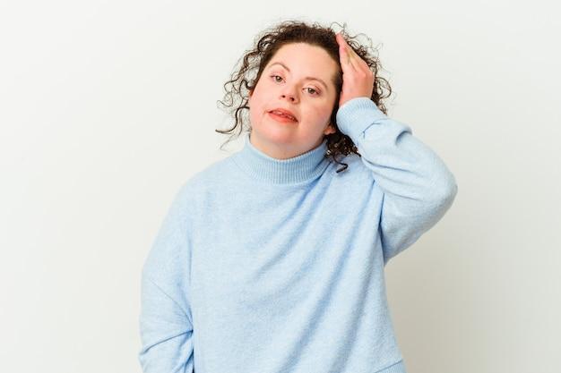 Mulher com síndrome de down isolada, esquecendo algo, batendo na testa com a palma da mão e fechando os olhos.