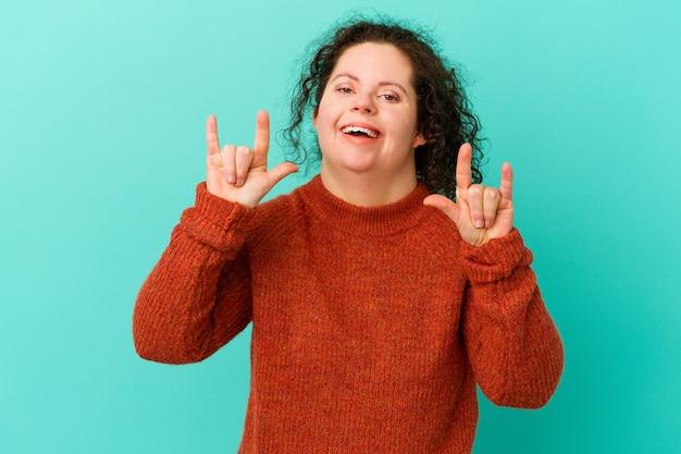 Mulher com síndrome de down isolada, mostrando um gesto de chifres como um conceito de revolução.