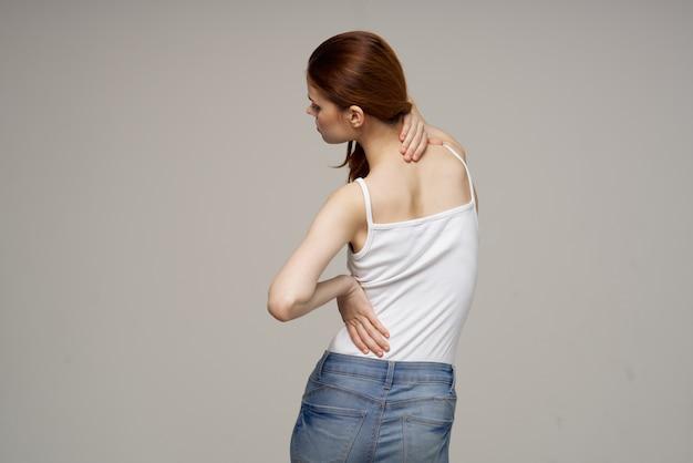 Mulher com sintomas de dor de t-shirt branca no tratamento de estúdio de artrite das articulações. foto de alta qualidade