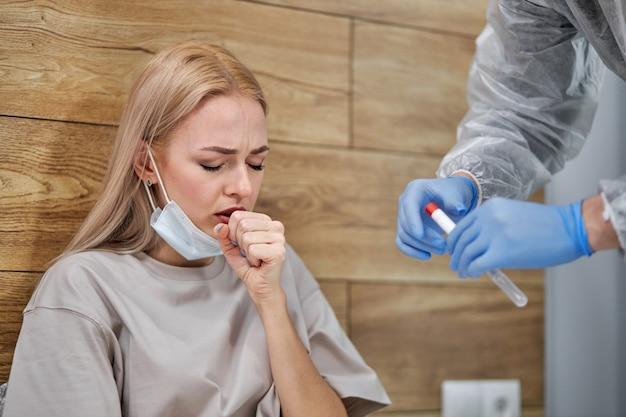 Mulher com sintomas respiratórios febre, tosse, dores no corpo sentada na cama em casa enquanto o médico se prepara para o exame médico, sofrendo de uma doença grave. quarentena, auto-isolamento, conceito de cuidados de saúde