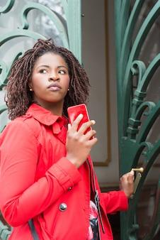 Mulher com smartphone, abrindo a porta e olhando de lado