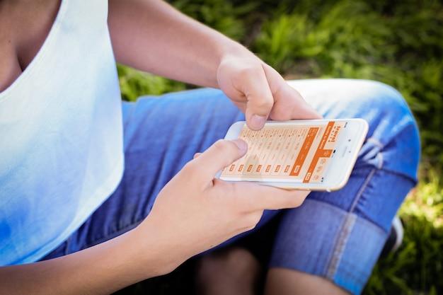 Mulher com smartphone comprando passagens aéreas em aplicativos móveis