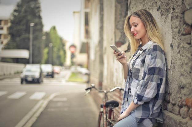 Mulher com smartphone e bicicleta