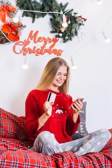 Mulher, com, smartphone, e, cartão plástico, cama