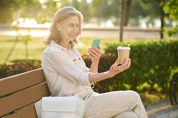 Mulher com smartphone e copo de café