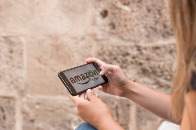 Mulher, com, smartphone, mostrando, amazon, principal, vídeo, app