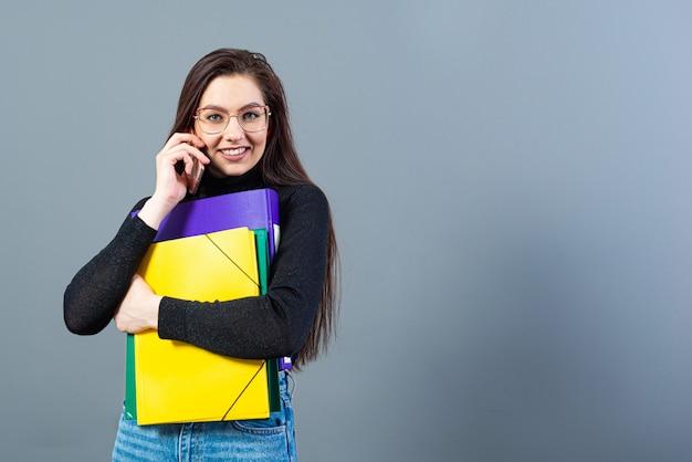 Mulher com smartphone segurando uma pasta colorida com documentos, isolados em uma superfície escura