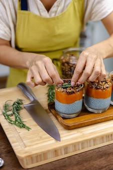 Mulher com sobremesas doces saudáveis e coloridas, pudins de chia feitos de leite de amêndoa, extrato de espirulina azul, sementes de chia, geleia de mamão e manga e granola caseira. na mesa de madeira na cozinha em casa.