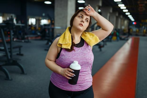 Mulher com sobrepeso bebe coquetel de dieta no ginásio, treinamento ativo. mulher obesa luta contra o excesso de peso, exercícios aeróbicos contra a obesidade, clube esportivo