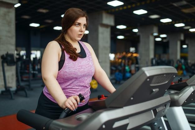 Mulher com sobrepeso, fazendo exercícios na esteira na academia, treinamento ativo. mulher obesa luta contra o excesso de peso, exercícios aeróbicos contra a obesidade, clube esportivo