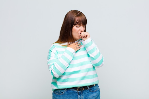 Mulher com sobrepeso passando mal, com dor de garganta e sintomas de gripe, tosse com a boca coberta